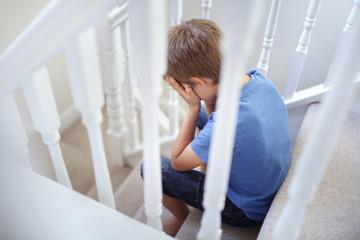 Upset problem child sitting on stairs