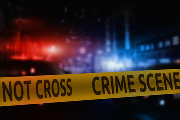 Crime scene tape on the background of night city lights and flashing lights of police cars