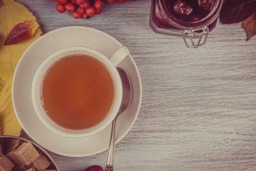 cup of tea on an old rustic wooden table with leaves of autumn, cane sugar cubes in a metal cup. copy space
