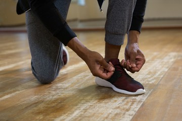Low section of dancer tying shoelace on floor