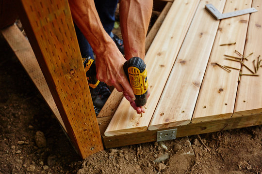 man drilling and measuring wood for deck