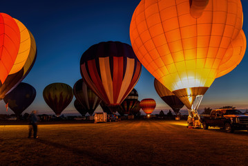 hot air balloons glowing in night sky
