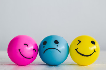 Emotions balls: Happy smiley face pink and yellow ball and depress sadness ball crying in the middle, concept: Why are you so sad?