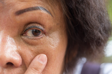 Asian elder women show her eyes and eyebrow tattoo