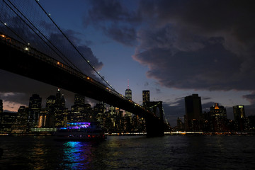 A ferry boat passes under Brooklyn Bridge in front of the night skyline of Lower Manhattan in New York City