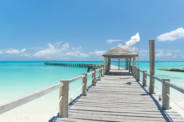 Wooden bridge with hut on the coast of azure Caribbean sea in hot sunny summer day
