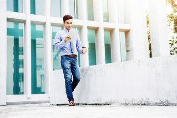 Working on Tablet, Soft focus of  Happy Young and Modern Businessman in casual wear using or reading tablet while Walk Outdoor, Lifestyle of modern male to use technology in business concept