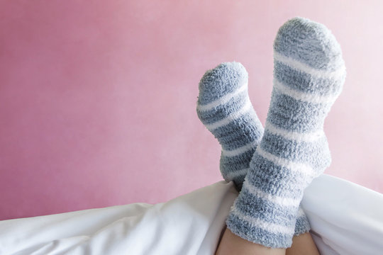 Relax and Cozy Concept, Female foot in Warm Stripe Wool Sock on Bed, Pink Pastel as background wall