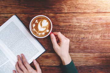 Reading and Relaxing Cozy in Cafe Concept, Focus on Hot Latte Coffee Cup on the wooden table, Lifestyle of Urban People, Top view