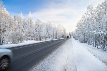 winter landscape with asphalt road,forest and blue sky.