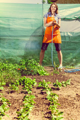Woman watering the garden with hose
