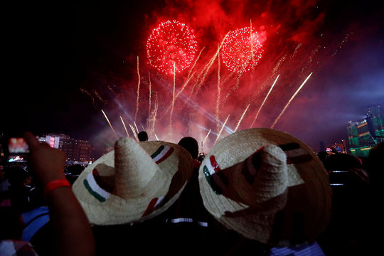 "Men wear traditional Mexican hats as they enjoy fireworks after the ""Cry of Independence"" by Mexico's President Enrique Pena Nieto, on the 207th anniversary of the day rebel priest Miguel Hidalgo set it on the path to independence, in Mexico City, Mexico"