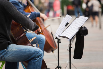 A group of musicians playing cellos on a street in a European city