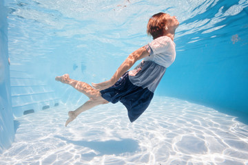 young woman in blue and white dress swim and dive underwater floating pool with transparent water in Beautiful Mysterious Underwater World. Fantastic Fairy dreamy fashion. Water safety class