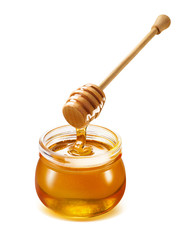 Honey dripping isolated from dipper into jar