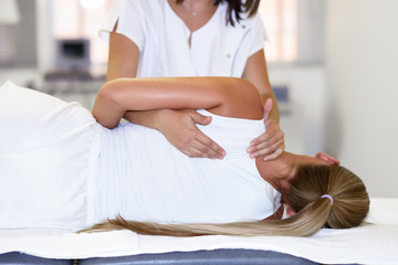 Professional female physiotherapist giving shoulder massage to blonde woman