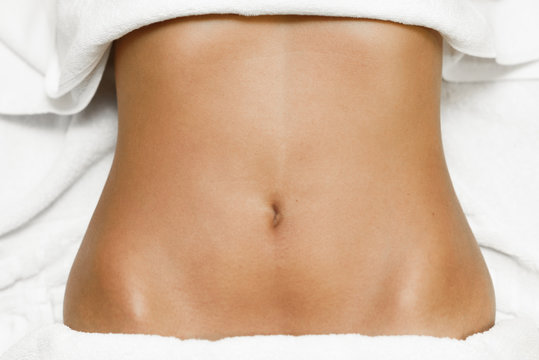 Top view of female abdomen laying on spa bed with white towels.