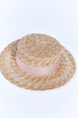 Straw hat of light straw with velvet ribbon beautiful stylish fashion accessory for summer resort on white background in studio.