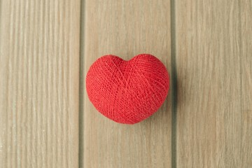 Creative red cotton heart on the wooden background. Top view. Valentine`s day background. Copy space.