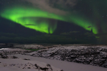 Aurora and clouds in the night sky in winter over the tundra and hills.