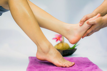 Spa treatment and product for feet spa with flowers and water, wooden background; select and soft focus.