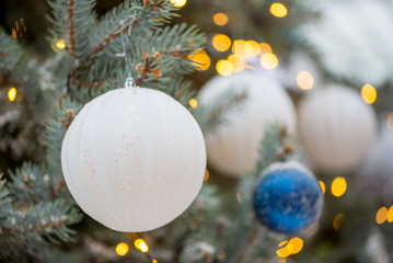 Close-up detail of a white, glittery Christmas oranment on a pale spruce tree, with bokeh lights in the background, Singapore. Xmas and family celebration concept.
