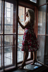 beautiful blonde poses near old windows in a building
