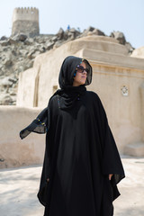 A beautiful western woman posing in the sunshine with her mobile phone tablet device, wearing a traditional arabic burka hijab dress. middle Eastern woman freedom and rights. Arabic fashion.