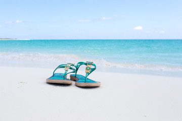 beach slippers on white sand on the background of azure sea