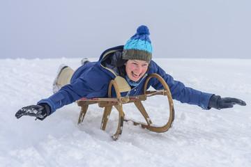 Tieffliegerin auf dem Rodel im Schnee