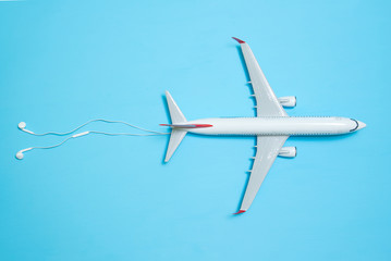 white airplane on a blue background with clouds