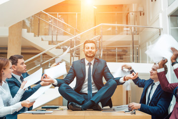 young handsome business man in black suit practice yoga and relax at office