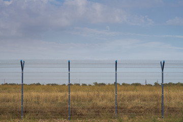 cage fence in fields, blue sky background