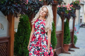Portrait of a beautiful blonde in dress in flowers