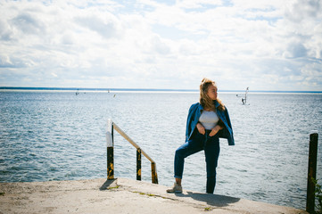 young beautiful woman in jeans clothes outdoors. portrait of a girl with freckles on her face, stylish girl on sea beach, on a sunny summer autumn day.