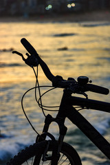 Silhouette of bicycle in front of the beach during sunset