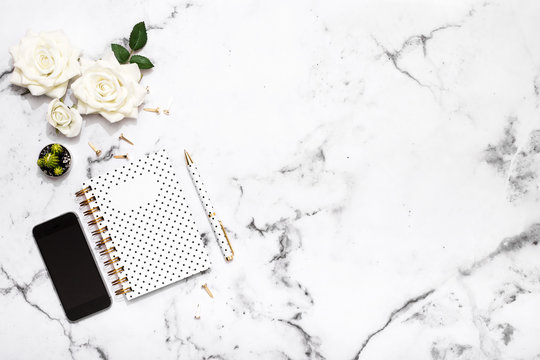 Marble table flat lay with gold stationary accessories, mobile phone, notebook and pen for wedding planning