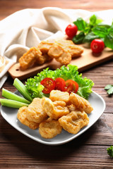 Tasty nuggets with vegetables on plate