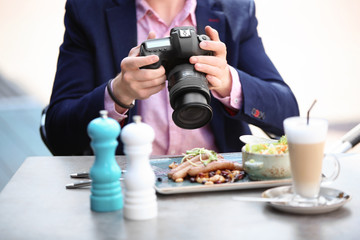 Young blogger working with camera at table, outdoors