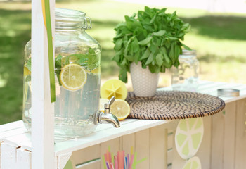 Lemonade in glass jar with tap on wooden stand outdoors