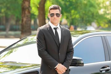 Handsome bodyguard near car outdoors