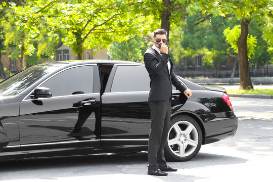 Handsome bodyguard near car outdoors