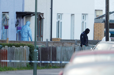 Investigators leave a property being searched after a man was arrested in connection with an explosion on a London Underground train, in Sunbury-on-Thames