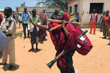 Somali Armed Forces member carries her ammunition during fighting between the military and police backed by intelligence forces in the Dayniile district of Mogadishu
