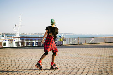 Young stylish funky girl with green hair riding roller skates and dancing near sea port during sunse