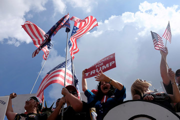 """Rally attendees wave flags and signs with """"Mother of All Rallies"""" slogans on the National Mall in Washington"""