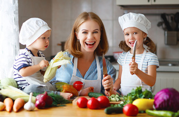 Healthy eating. Happy family mother and children  prepares   vegetable salad in kitchen.