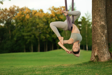 Young woman practicing aerial yoga on tree in park