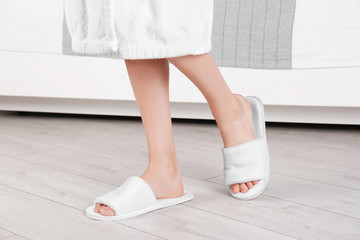 Woman standing in white spa slippers on grey parquet