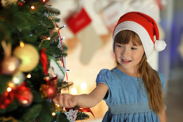 Cute little girl in Santa hat decorating Christmas tree at home